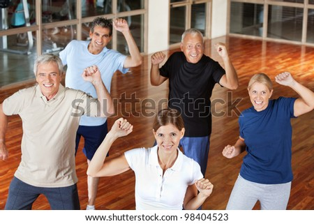 Happy senior group moving and dancing in fitness center - stock photo
