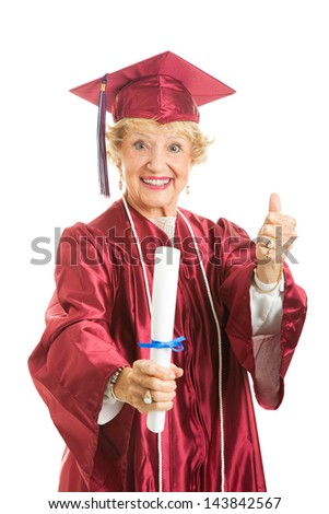 Happy senior lady graduates in her cap and gown, giving thumbs up. - stock photo