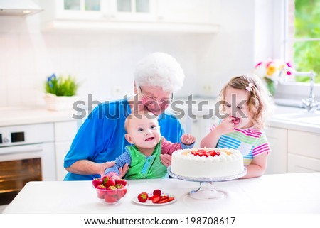 Happy senior lady, loving grandmother, baking a homemade strawberry cake with two children, cute laughing baby boy and adorable curly toddler girl, in a white modern kitchen with window - stock photo
