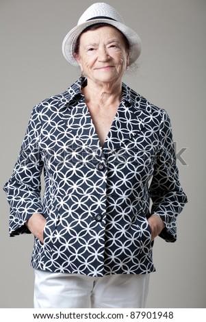 Happy senior lady posing on gray background. - stock photo