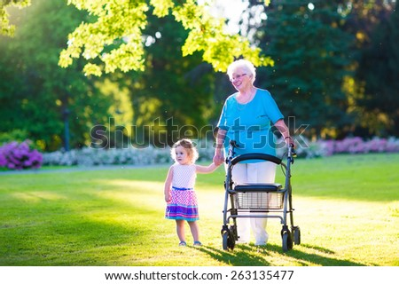 Happy senior lady with a walker or wheel chair and a little toddler girl, grandmother and granddaughter, enjoying a walk in the park. Child supporting disabled grandparent. - stock photo