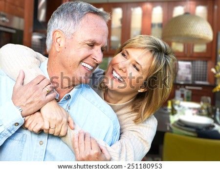 Happy senior loving couple over house background - stock photo
