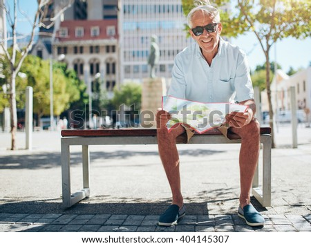 Happy senior male sitting on bench with a city map. Mature caucasian man sitting outdoors holding a map. - stock photo