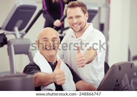 Happy senior man and physical trainer working together in a gym giving a thumbs up of approval and success in a healthy lifestyle concept - stock photo