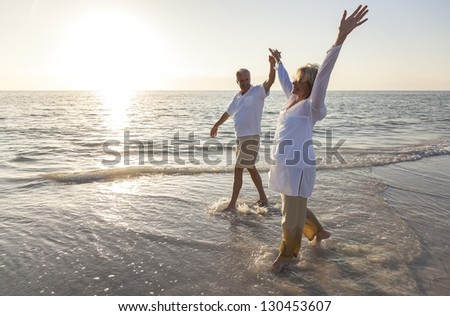 Happy senior man and woman couple dancing and holding hands on a deserted tropical beach at sunrise or sunset - stock photo