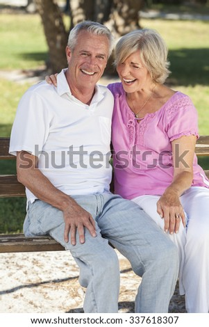 Happy senior man and woman couple sitting laughing together on a park bench outside in sunshine - stock photo