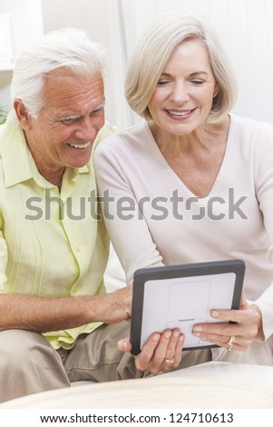 Happy senior man and woman couple sitting together at home on a sofa using a tablet computer - stock photo