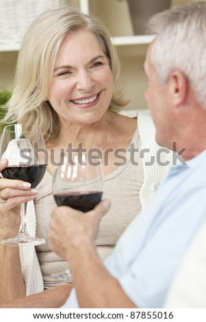 Happy senior man and woman couple sitting together at home smiling and drinking wine - stock photo