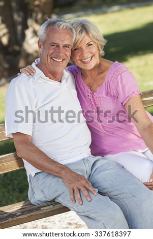 Happy senior man and woman couple sitting together laughing on a park bench outside in sunshine - stock photo