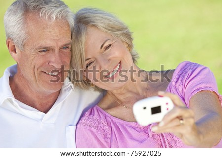 Happy senior man and woman couple sitting together outside in sunshine and taking a self portrait on digital camera - stock photo