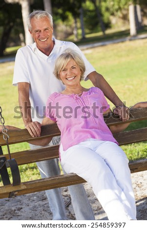 Happy senior man and woman couple sitting together outside in sunshine on a park bench - stock photo