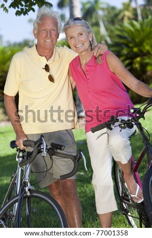 Happy senior man and woman couple together cycling on bicycles outside in a sunny green park - stock photo