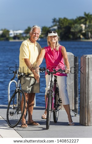 Happy senior man and woman couple together cycling on bicycles with bright clear blue sky by a river or sea - stock photo