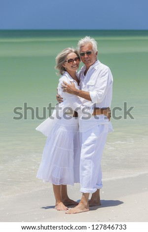 Happy senior man and woman couple together embracing by sea on a deserted tropical beach with bright clear blue sky - stock photo