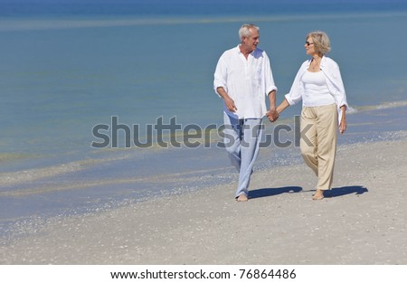 Happy senior man and woman couple together holding hands and walking on a deserted tropical beach - stock photo
