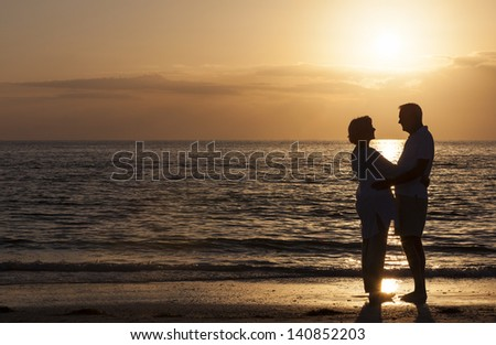 Happy senior man and woman couple together hugging embracing at sunset on a deserted tropical beach - stock photo