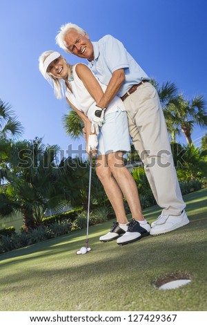 Happy senior man and woman couple together playing golf and putting on a green, the man is teaching the woman how to put. - stock photo