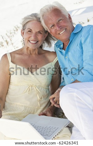 Happy senior man and woman couple together using a white laptop computer on a beach. - stock photo