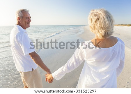Happy senior man and woman couple walking and holding hands on a deserted tropical beach with blue sky and golden evening light - stock photo