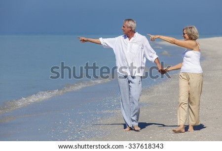 Happy senior man and woman couple walking, holding hands and pointing to sea on a deserted tropical beach with bright clear blue sky - stock photo