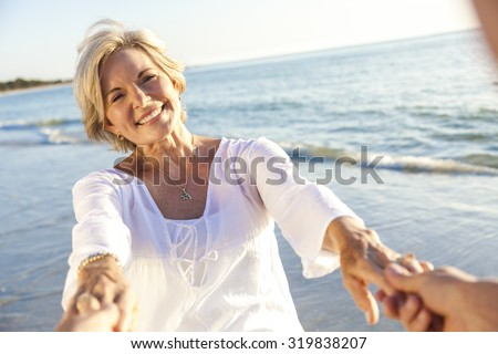 Happy senior man and woman couple walking or dancing and holding hands on a deserted tropical beach  - stock photo