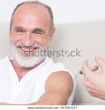 Happy senior man being vaccinated  - stock photo