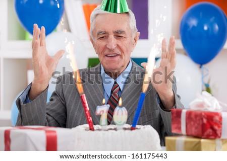 Happy senior man celebrating 70th birthday - stock photo