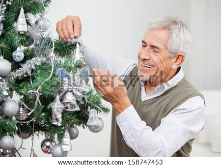 Happy senior man decorating Christmas tree at home - stock photo