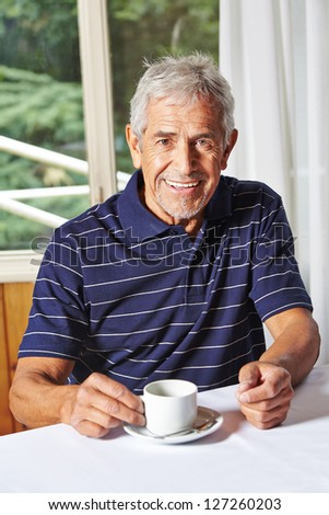 Happy senior man drinking a cup of coffee in a nursing home - stock photo