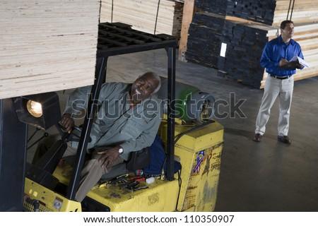 Happy senior man driving forklift - stock photo