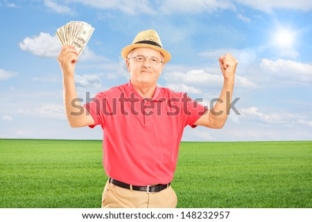 Happy senior man holding money banknotes and gesturing happiness on a field - stock photo