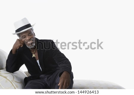 Happy senior man in fedora sitting on chaise lounge against white background - stock photo