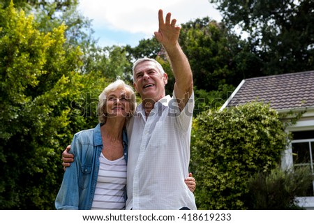 Happy senior man pointing while standing with wife in back yard - stock photo