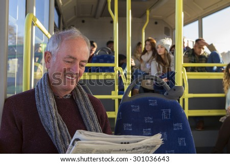 Happy senior man reading a newspaper on the bus.  - stock photo