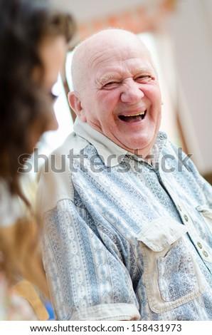 Happy senior man sitting indoor - stock photo