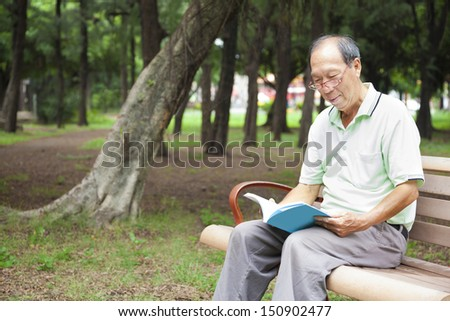 happy senior man sitting on  bench and reading  book - stock photo
