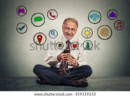 Happy senior man sitting on floor using texting on smartphone browsing web social media application icons flying out of cellphone isolated grey background. 4g data plan. Communication tech concept - stock photo