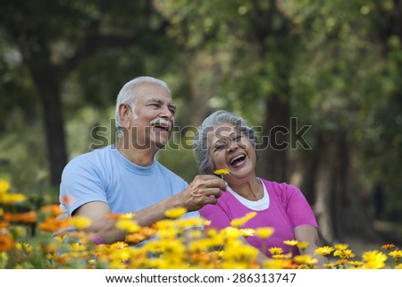 Happy senior man smiling with woman at park holding flower - stock photo