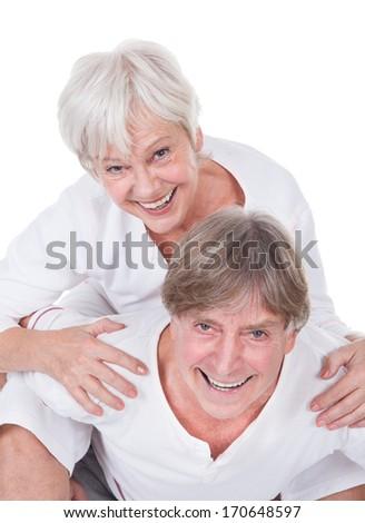 Happy Senior Man Taking A Piggyback To Woman Over White Background - stock photo