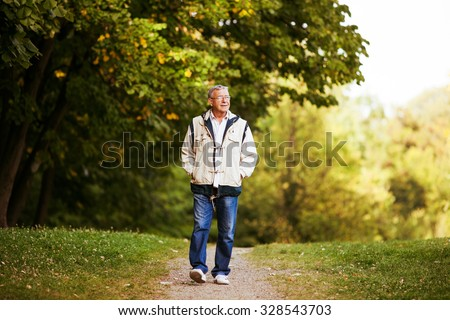 Happy senior man walking and relaxing in park - stock photo