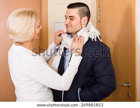 Happy senior mother helping adult son to tie a scarf  - stock photo