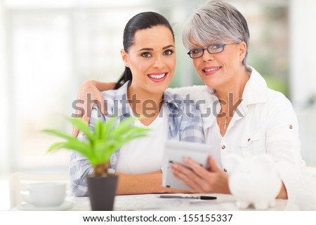 happy senior mother helping daughter calculate her finances - stock photo