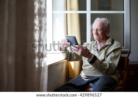 Happy senior relaxing at home and using tablet. - stock photo