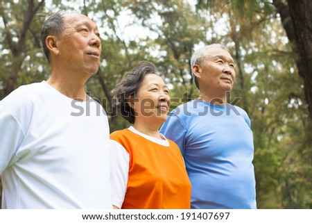 happy senior sibling standing a row in park - stock photo