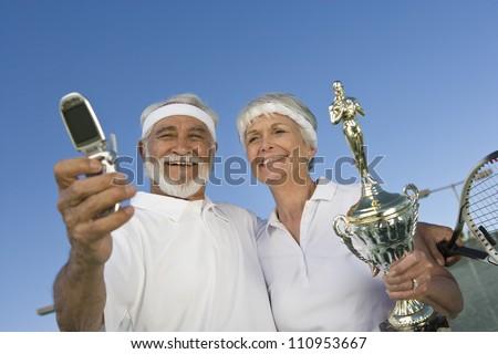 Happy senior tennis player holding trophy - stock photo