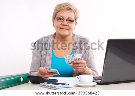 Happy senior woman, an elderly pensioner counting currency money for utility bills at her home, concept of financial security in old age - stock photo