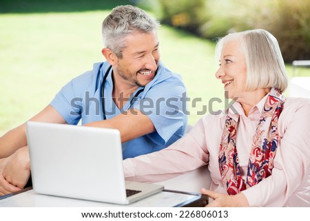 Happy senior woman and caretaker looking at each other while using laptop on nursing home porch - stock photo