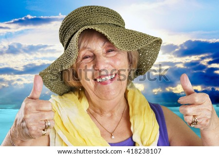 Happy senior woman at the beach two thumbs up - stock photo