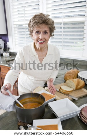Happy senior woman cooking soup in kitchen - stock photo