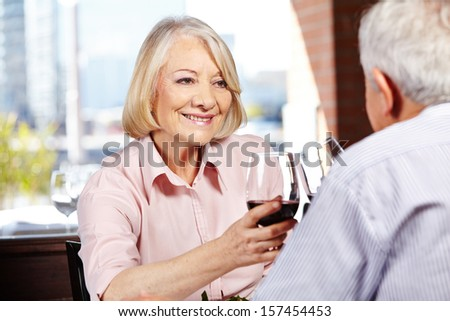 Happy senior woman drinking a glass of red wine with her husband in a restaurant - stock photo